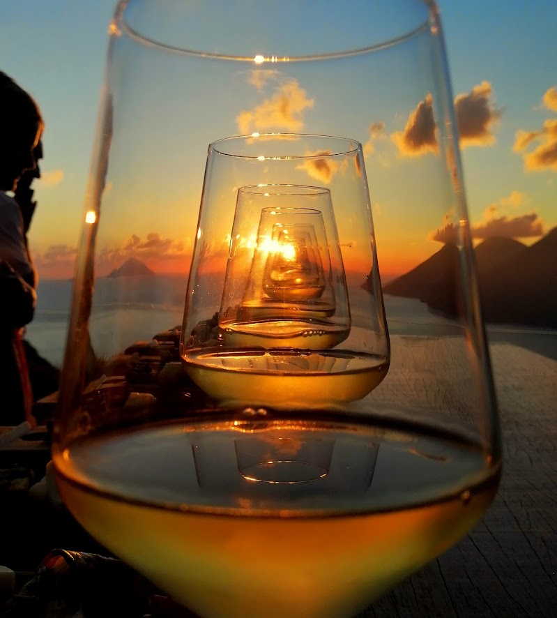 L'incanto di un tramonto Eoliano attraverso un bicchiere di vino  di alessia_mar