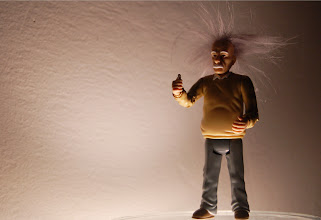 Photo: Requirement 3 (portrait of an object): The action figure of Einstein is one of my favorite objects. He holds a piece of chalk in his outstretched hand, and his hair is as unruly as ever. I set him against a textured white wall, lit from below. He stands on an upside-down glass plate that allows an incandescent bulb to shine its light up without too much interference. I like the somewhat humorous and mysterious feel of the photo... With the light from below, Einstein gives off an aura -- his hair, hands, and face illuminated; he's deep in thought, about to step forward and uncover another theorem... Humorous because he is, after all, an Einstein action figure. Post-processing: cropped, slight adjustment of brightness around the crotch :)