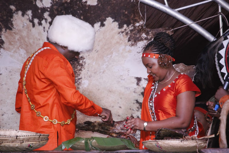 Waiganjo cuts the meat as Waiguru holds