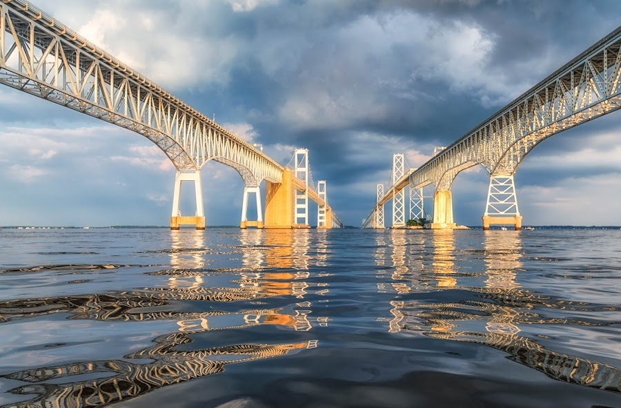 Storm at the Bridge by Carol Ward - Buildings & Architecture Bridges & Suspended Structures ( annapolis, chesapeake bay bridge, between the bridge spans, maryland, reflections, chesapeake bay, architecture, storm clouds, bridge, storm, beneath,  )
