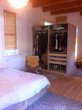 "Photo: This is one-half of the ""closet"" storage space; the other side has the same drawer/shoe set up, but two 1/2-as-long hanging shirt racks, instead of the long dress rods you see on this side. Over the top of the ""closet"" you can see the wooden entry into a storage area, which is above the entry to the basement."