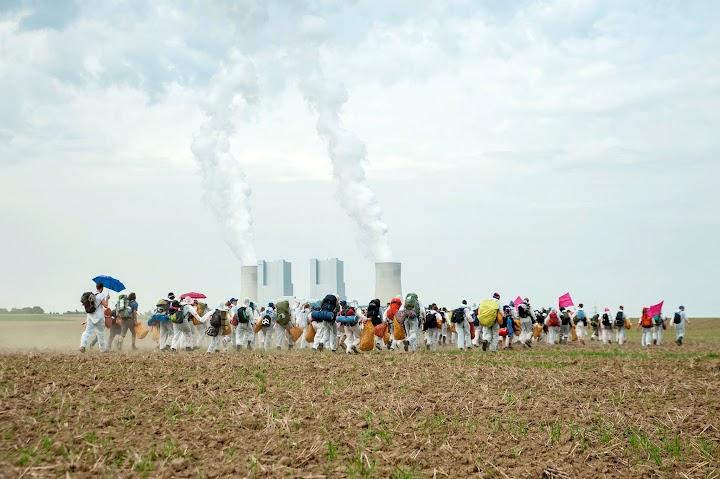 Demonstranten auf dem Acker vor Kohlekraftwerk.