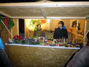 Photo: Maria Denner, Organisatorin der Adventkranzflechterei, und Herr Braunsteiner jun. auf ihrem Verkaufsstand.