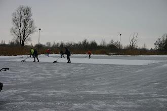 Photo: Met man/vrouw en macht wordt de ijsbaan sneeuwvrij gemaakt.