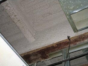 Photo: Asbestos sprayed-on fireproofing on the steel beam and deck.  The photo shows the asbestos fireproofing was removed from the bottom of the steel beam to install wall studs.  At the time of the removal this probably caused asbestos exposure to the workers working on the wall.