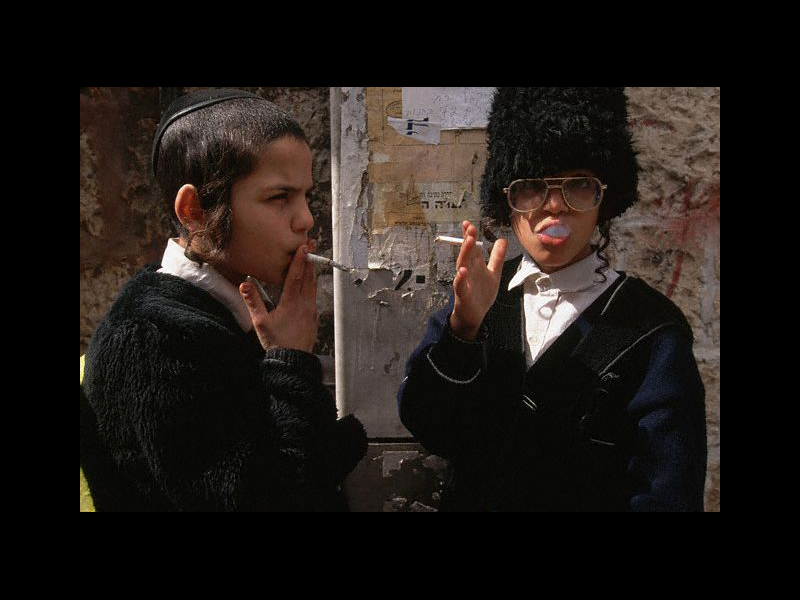 Photo: April 1995, Jerusalem, Israel --- Two boys dress up and smoke cigarettes on Purim, when people dress up and celebrate the rescue of Persian Jews by Queen Esther. Mea She'arim is a strictly religious Jewish district. --- Image by © Annie Griffiths Belt/CORBIS