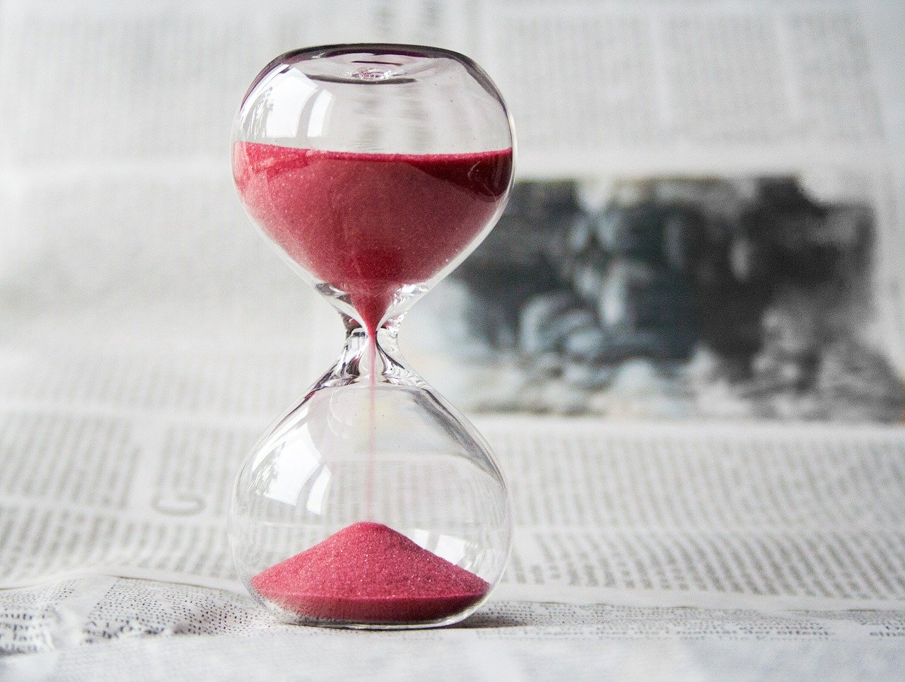 An hourglass on top of a newspaper