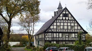 Photo: Frisch renoviert: Giebelfront des Gutshauses Funckenhausen. Im Hintergrund (links) der Kaisberg und der 220 m hohe Schornstein des Cuno-Kraftwerks (Herdecke).