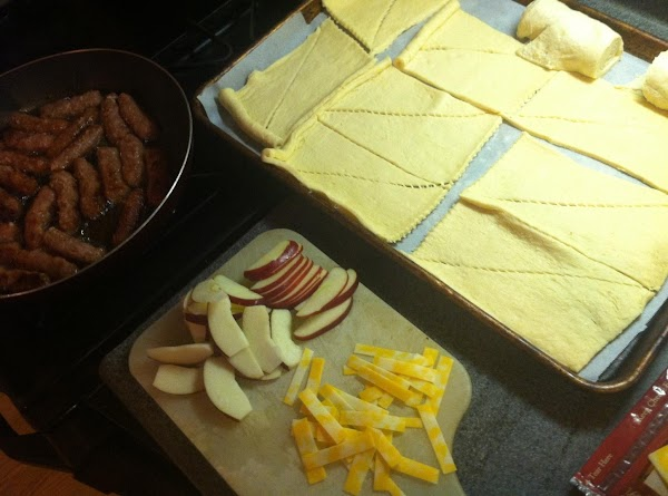 Roll out both packages of crescent rolls flat and pull apart the triangles. Do...