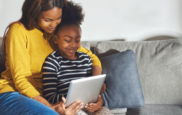 A mother and her daughter sitting and looking at a tablet together while smiling