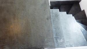 palier d'escalier en béton ciré couleur acier appliqué par un applicateur spécialisé dans le béton ciré
