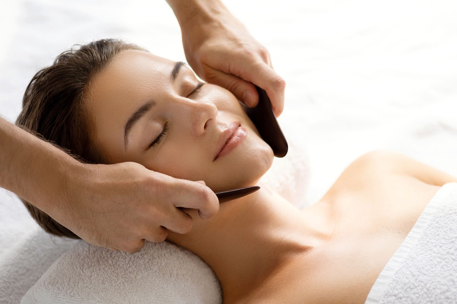 A woman getting a gua sha facial from a medical spa