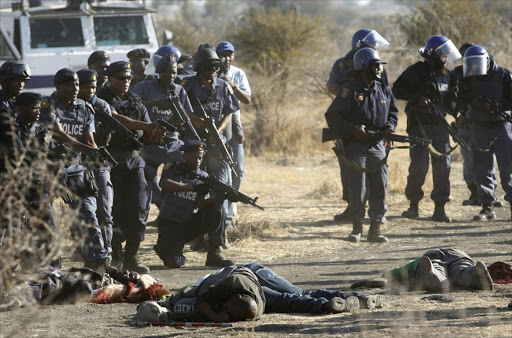 Policemen surround the dead and wounded immediately after the shooting at Marikana mine. Picture: REUTERS