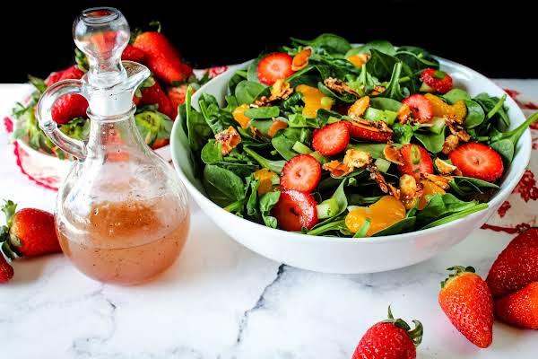 A Bowl Of Mandarin Orange Strawberry Salad With Dressing On The Side.
