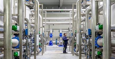 Un tecnico che controlla le grandi tubature, alte fino al soffitto, di un impianto di trattamento delle acque presso il data center di Google in Belgio.
