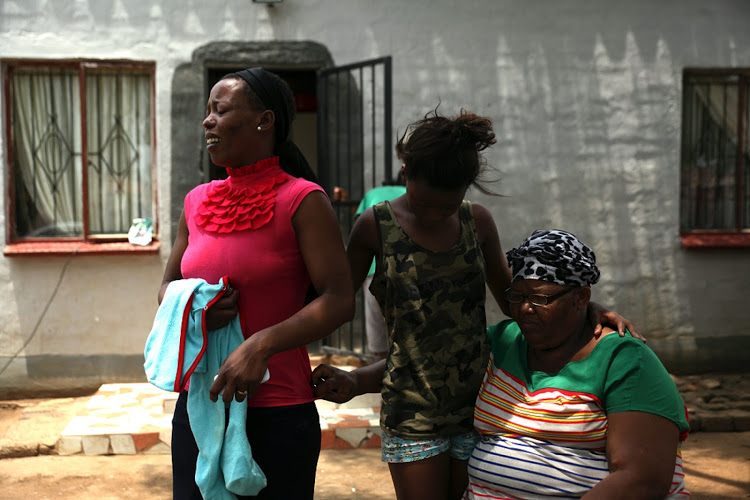 Mother Uzelle Maine cries as she stands in the spot where her son Siyabong Buthalezi was shot in Windmill Park, Boksburg. Next to her is daughter Letazz Maine and Buthelezi's grandmother Bernadette Lange.