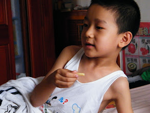 Photo: baby son warrenzh 朱楚甲, owner of warozhu.com and wozon.net, watching comic online while eating potato chips.