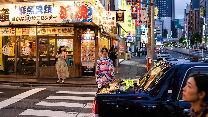 Intersección de calles repleta de luminosos mientras una joven con kimono cruza un paso de cebra (Foto: Chema Artero).