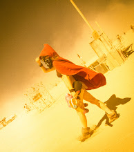 Photo: The Hooded Wanderer  So, if you look through my other Burning Man photos, you'll see I have a some steampunk goggles that have orange lenses.  Everything I see has a strange orange and grainy tint.  All I see are oranges and reds.  The reds pop like something out of the spectrum.  I spent a small eternity in Lightroom re-creating the effect.... so, in many ways, you are seeing exactly what I am seeing.  The esplanade is a street that is in the inner edge of the 50,000 inhabitants of Burning Man.  It's the most efficient ways of traveling from one place to another... and it's the best for people-watching, if you're into this sort of thing.