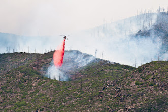 Photo: Helicopter drops fire retardant on patch of fire.