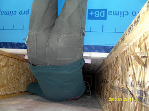 """Photo: Owner/designer guy hangs down over edge of roof to take pic of builder guy's butt as he reaches into roof cavity (DPC cavities are 3' x 16"""") to run ethernet monitoring wires."""