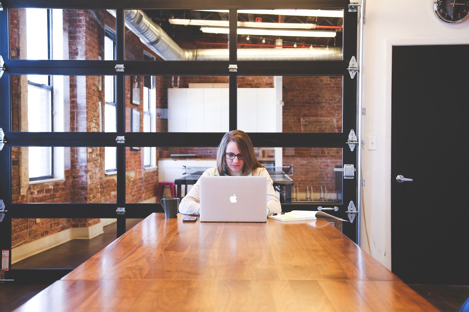 A woman on a wooden desk working on her laptop