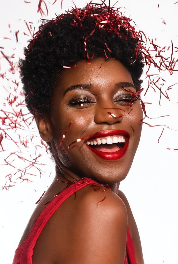 foto de uma mulher negra sorrindo com papelzinhos vermelhos caindo nela como se fosse uma celebraçaõ