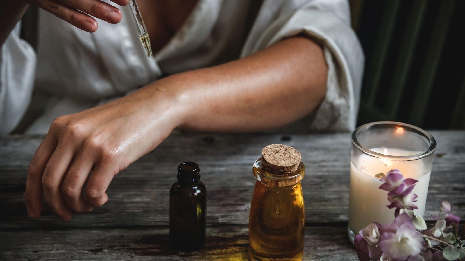 An aromatherapist drops essential oils onto her wrist.