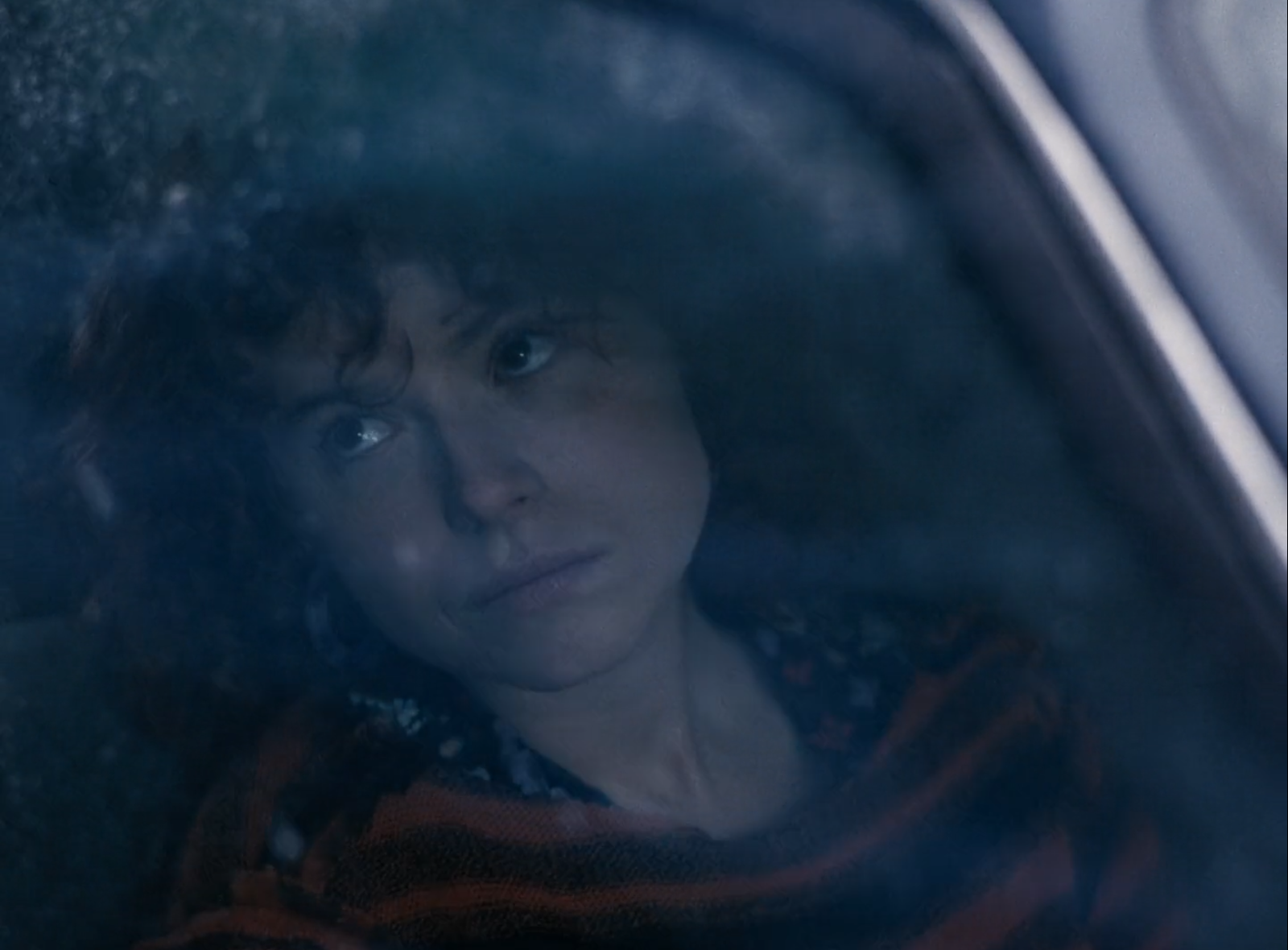 Jessie Buckley in I'm Thinking of Ending Things (2020). Lucy, a young white woman with curly ginger hair and wearing a black floral dress, is filmed looking out from behind a car window, glazed over with blue shadow and slightly out of focus. She looks upwards, morose.