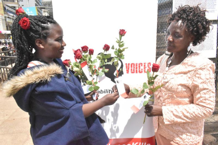 Mercy Langat, an official from Missing Voices project, hands roses to Mama Victor in Nairobi on February 14, 2020.