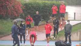 Los jugadores llegando al campo Anexo bajo la lluvia.