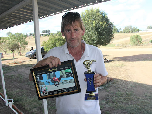 Boggabri greyhound trainer Andrew Bell with the recognition of Flatlined's Gardens win in April, 2015, and with a trophy which Chilling Fantasy won at the Coona Hotel Maiden on Easter Monday last year.