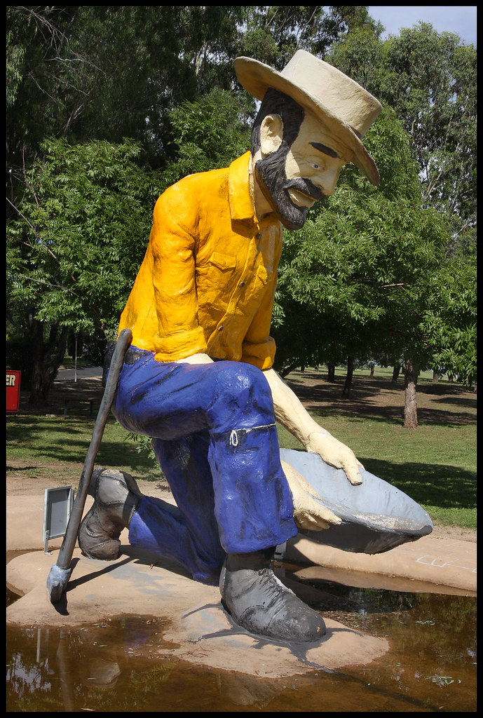 the big gold panner wearing a yellow shirt and blue jeans looking for gold