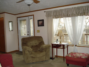 Photo: The living room windows show a lovely view of lake. All window treatments stay.