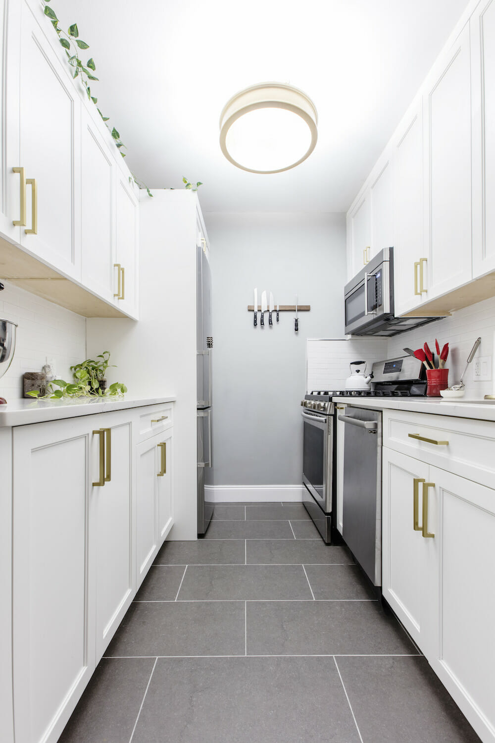 narrow galley kitchen remodel with white shaker cabinets, brass hardware and a large ceiling light that mimics natural light