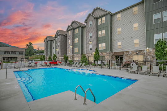 Pool area featuring lounges overlooking apartment building at dusk
