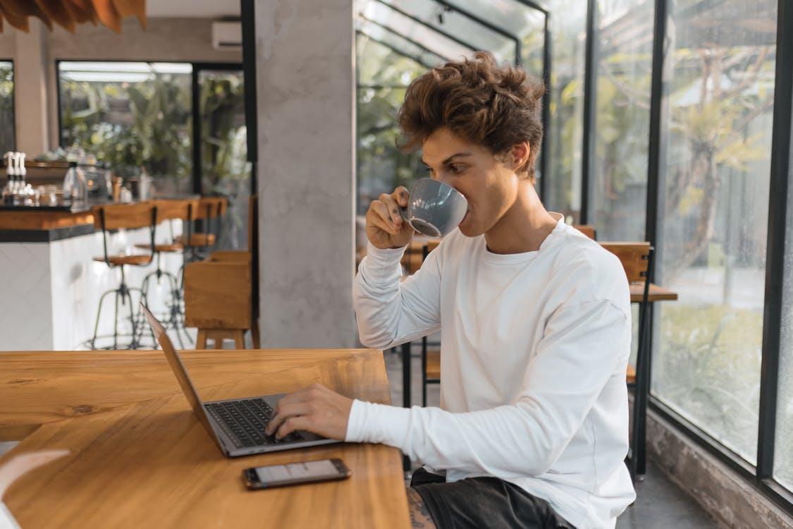 Man in White Long Sleeve Shirt Holding Black Ceramic Mug Sitting Beside Brown Wooden Table
