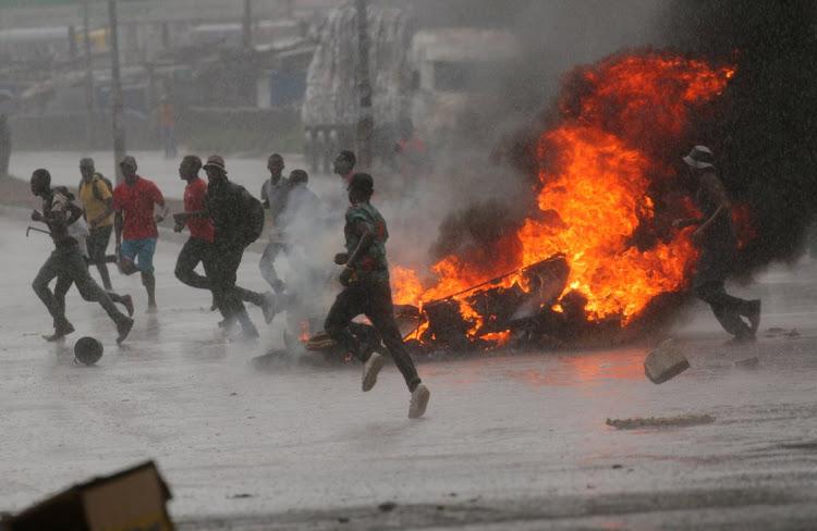 People run at a protest as barricades burn during rainfall in Harare, Zimbabwe. Picture: REUTERS/PHILIMON BULAWAYO