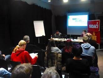 Veranstaltungsbesucher und Podium mit SDAJ- und KKE-Transparenten.