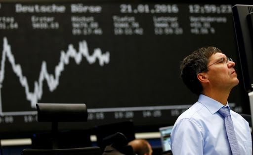 A trader works at his desk in front of the German share price index, DAX board, at the stock exchange in Frankfurt, Germany. File photo: REUTERS
