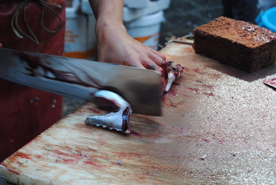 A fishmonger slices fish with a large blade on a wooden board. He uses his other hand to wipe away blood.