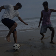 Two men playing soccer on the beach while barefoot