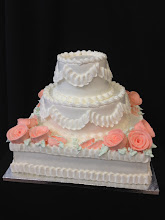 Photo: Mixed 3-tier wedding cake featuring a square bottom tier with two round cakes on top. Ribbon ruffle border w/peach frosting roses.