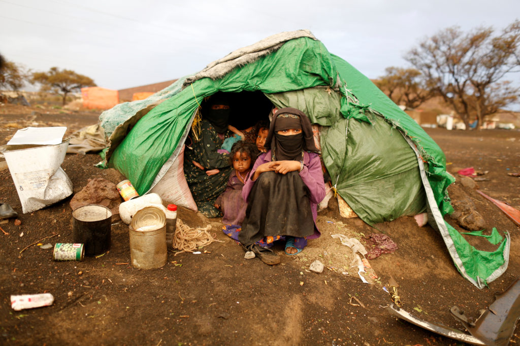 A mother sits at the door of a tent in a camp for internally displaced people in Yemen