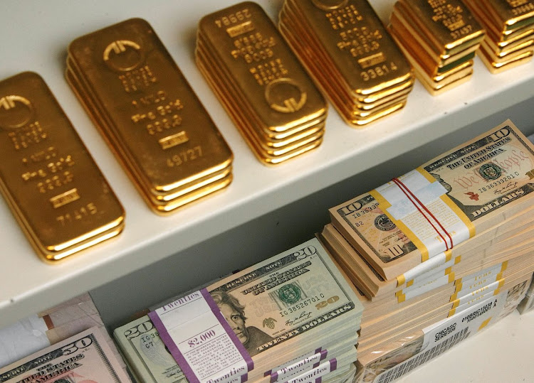 Gold bars and dollar bills are pictured in a safe in a bank in Vienna. Picture: REUTERS/HEINZ-PETER BADER