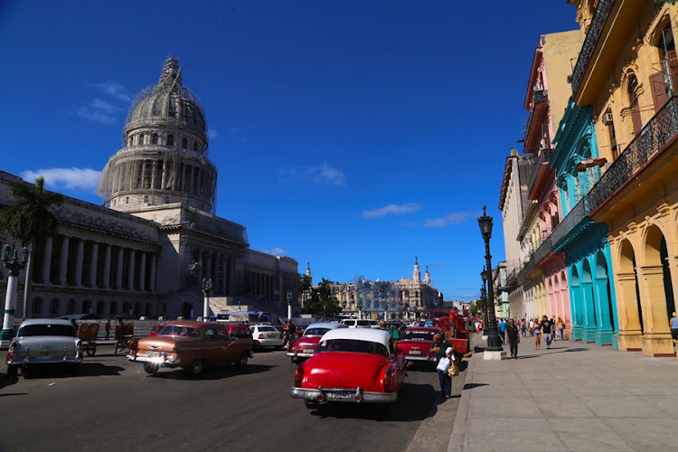 Cars passing by the colourful buildings of Havana, Cuba.