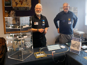 Photo: 016 In a separate room I found the 009 Society publicity desk, with Society Archivist Garry Whiting on the right and Hugh Norwood who was demonstrating his hand generated controller that he has very cleverly made from one of those hand powered torches. It works as well – speed of train dependant upon speed of turning the handle, forget all this feedback and pulse power stuff! .