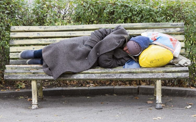 Homeless man sleeping on a bench.