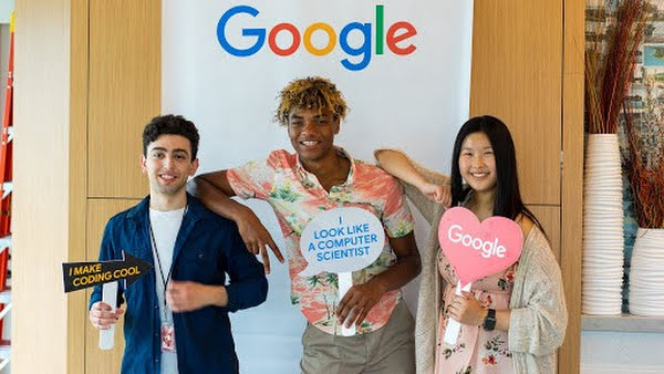 Three students who are learning coding stand in front of the Google logo