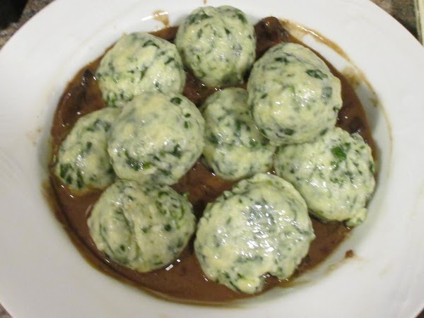 Spoon the mushrooms and sauce into individual bowls.  Place buttered and oiled gnudi...